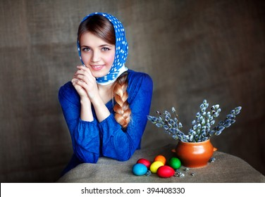 Beautiful young girl in blue scarf and dress sitting at the table with colorful Easter eggs and pussy willow. Portrait of pretty model with long shiny braid. Easter holiday. Smiling woman.