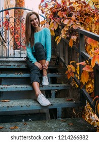 Beautiful young girl in a blue sweater, sitting on the steps of the veranda, enjoying the autumn landscape