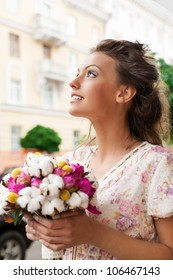 beautiful young girl with bouquet of flowers. Outdoors