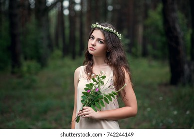Beautiful young girl with a bouquet and a wreath of wildflowers in her hair.