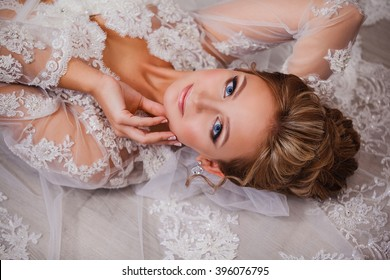 Beautiful young girl bride with fashion wedding hairstyle . Portrait of a young gorgeous bride in wedding white dress with a train , garter , veil , blue eyes . Wedding.