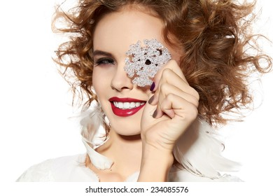 Beautiful young girl with a bright evening make-up of shiny red lipstick long fluffy eyelashes blond curly hair holding snowflake near the face winter knitted sweater New Year Christmas joy happiness