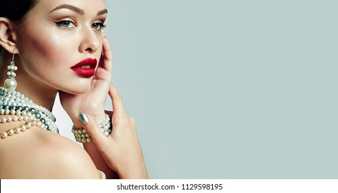 Beautiful young girl with bright lips in studio at half a turn. Jewelry pearl jewelry - earrings, bracelet, necklace.