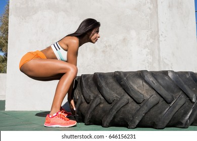 Beautiful young girl in bright sexy shorts with pretty athlete muscular body lift up big heavy tire. Crossfit training urban area street gym city exercise routine healthy lifestyle. Fit butt ass.