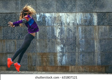 Beautiful young girl in bright sportswear doing exercises on the streets near the wall, urban style