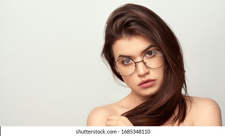 beautiful young girl with brown hair in fashionable glasses posing on a white background with bare shoulders, empty space for text