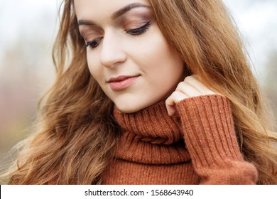 Beautiful young girl in a brown sweater. Close-up. The concept of autumn, tenderness, cosmetics and makeup.