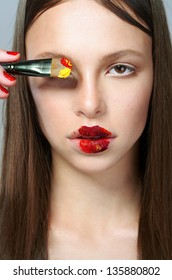 the beautiful young girl a brush makes up lips with paint, lipstick, a portrait