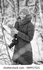 beautiful young girl with a camera in a winter forest