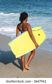 Beautiful young girl carrying her body board.