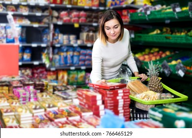 Beautiful young girl choosing delicious sweets in supermarket