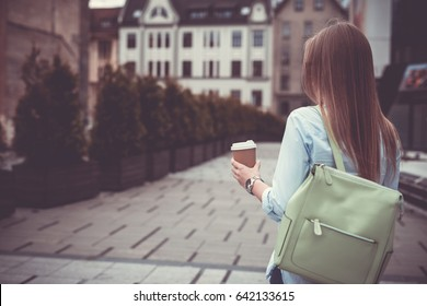 Beautiful young girl in the city drinking coffee and chatting