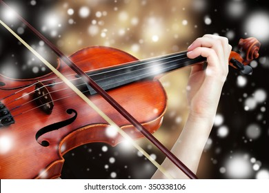 Beautiful young girl with classical violin on bright background over snow effect