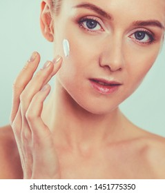 The beautiful young girl with a clean fresh skin touches with a hand a cheek