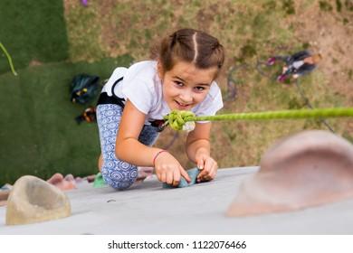 Beautiful young girl climbing to big artificial wall