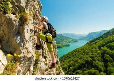 Beautiful young girl climbing Drachenwand via ferrata high above scenic Mondsee lake, Austria
