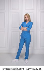 Beautiful young girl in the clothes of a nurse posing in a photographic studio. Fashionable stylish clothes for medical personnel, doctors, cosmetologists.