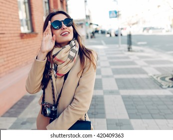 Beautiful and young girl in a coat and scarf and sunglasses walking around the city in the summer.