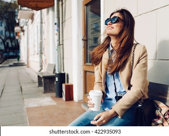 Beautiful and young girl in a coat and scarf and sunglasses sitting on the bench. Woman drinking coffee and laughing. Summer.