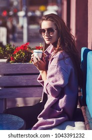 Beautiful and young girl in a coat and sunglasses sitting on the bench.