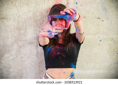 Beautiful young girl with color holi focusing with her fingers