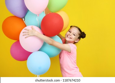 Beautiful young girl with colored balloons on yellow background