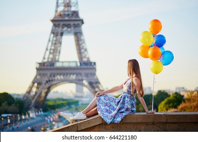 Beautiful young girl with colorful balloons near the Eiffel tower in Paris, France