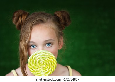 Beautiful young girl with colorful lollipop .