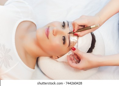 Beautiful young girl correction of eyebrows in a salon.professional care for face.Permanent Makeup for brows. woman tweezing her eyebrows in salon.Cosmetology Treatment.Make-Up.Microblading eyebrows.