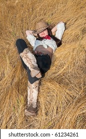 beautiful young girl is a cowboy, is resting in a field