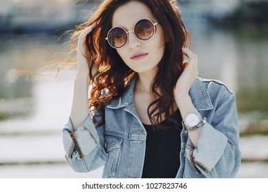 A beautiful young girl with curly hair and glasses standing by the water