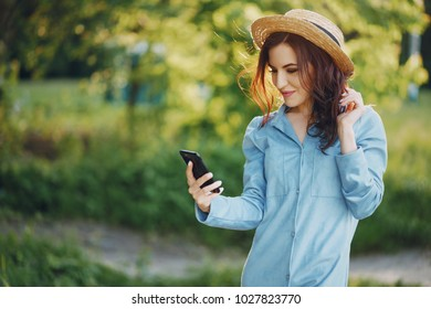 A beautiful young girl with curly hair and straw hat in the summer park