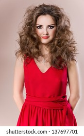 Beautiful young girl with curly hair, girl in red dress, posing in studio