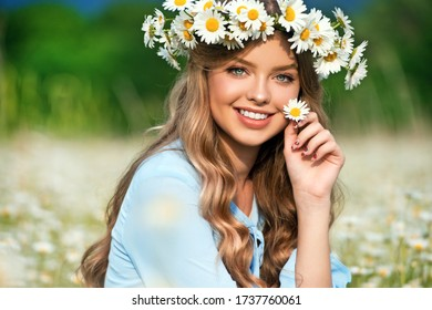 Beautiful young girl with curly hair in chamomile field.  Beautiful girl with chamomile wreath and blue dress on flowering field in summer. Beautiful curly hair. Freedom concept.