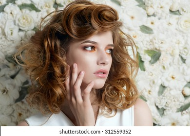 Schönes junges Mädchen mit lockigen Haaren auf weißen Blumen, das Konzept der Schönheit