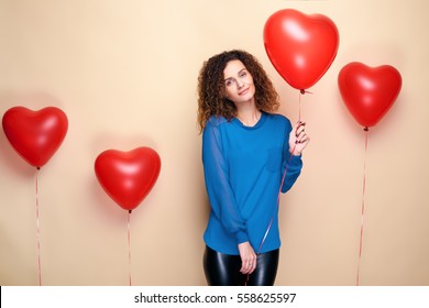 Beautiful young girl with curly hair and blue sweater holding a few red heart air balloon and smiling. The concept of Valentine's Day