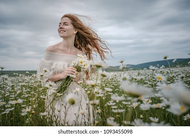 Beautiful young girl with curly red hair in chamomile field. Concept and idea of a healthy lifestyle, skin and hair care