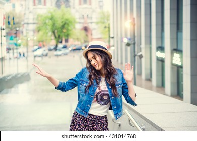 Beautiful young girl dancing on the stairs of building. A woman dressed in casual style. Girl on the background of the city. Sunset.
