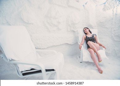 beautiful, young girl with dark hair in swimsuit on chaise longue in salt room, Spa therapy to improve breathing