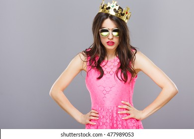 Beautiful young girl with dark hair and red lips wearing pink dress, sunglasses and crown posing at gray studio background, portrait, copy space.