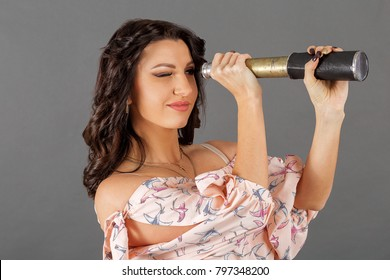 A beautiful young girl with a dark hair color looks in a telescope on a gray background close up