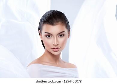 Beautiful young girl with dark wet hair and nude make up wearing white clothes at studio background, clouds concept, beauty photo.