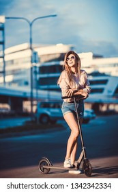 Beautiful young girl in a denim shorts riding an electric scooter,  in  sunglasses with long hair, street style, city, smiles and pleasure, for fan, hipster, driver, emotional
