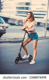 Beautiful young girl in a denim shorts riding an electric scooter,  in  sunglasses with long hair, street-style, city, smiles and pleasure, for fan, hipster, driver, emotional