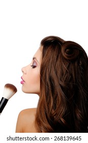 Beautiful young girl does makeup isolated on white