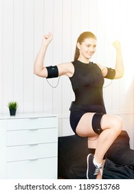Beautiful young girl doing exercises on the machine for muscle stimulation. Innovative technology of exercise and fitness. Exercises for women on the electro-muscular machine.