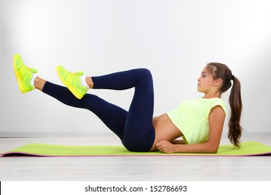 Beautiful young girl doing exercises at home