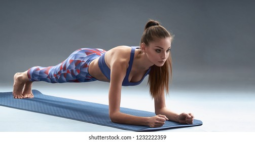 Beautiful young girl doing plank on yoga mat.