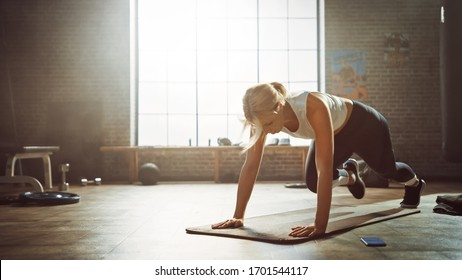 Beautiful and Young Girl Doing Running Plank Exercise on Her Fitness Mat. Athletic Woman Does Mountain Climber Workout in Stylish Hardcore Gym