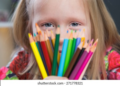 Beautiful young girl drawing with color pencils